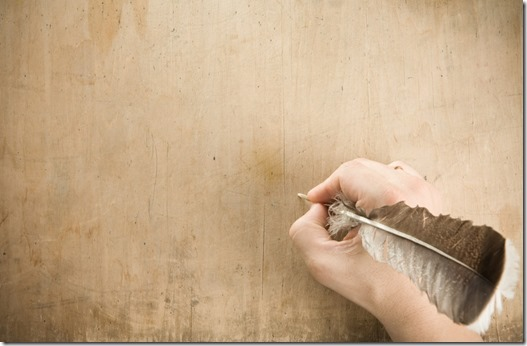 Hand holding quill pen preparing to write on blank parchment
