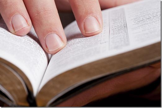 Fingers on open Bible
