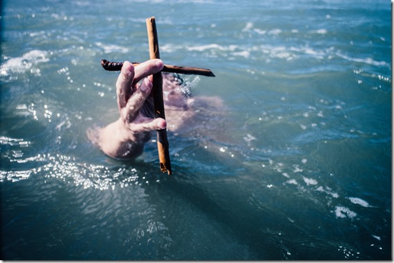 Man holding cross in the sea