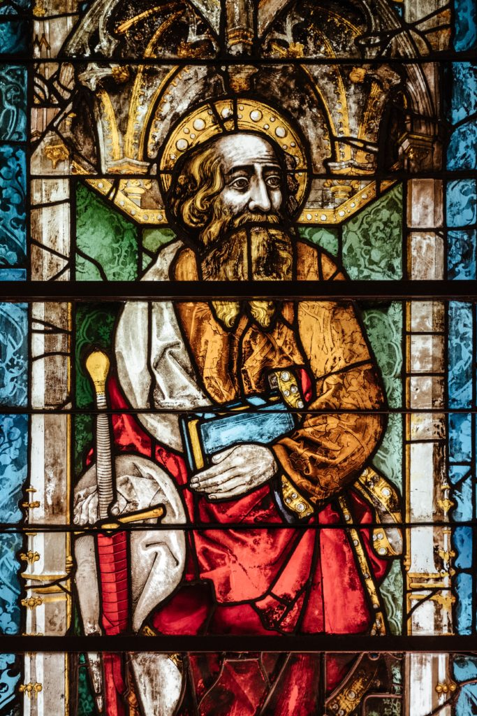 Stained glass image of saint holding a Bible and a sword