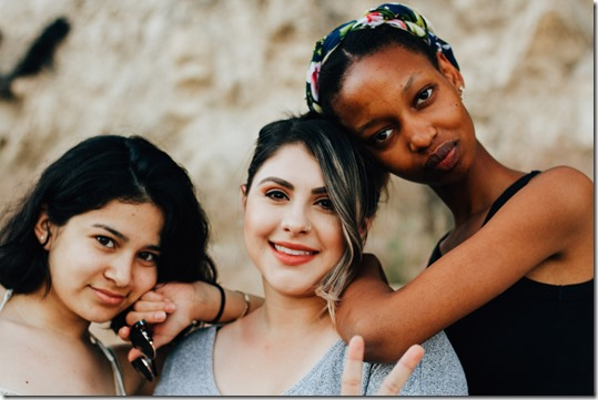 Three women friends and a peace sign